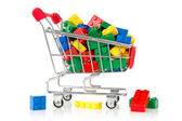 Color plastic bricks in a shopping cart — Stock Photo