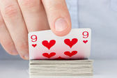 Hand revealing nine of hearts — Stock Photo