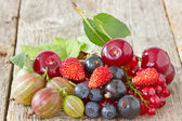 Assorted berries on the wooden floor — Stock Photo