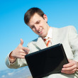 Smiling businessman with laptop — Stock Photo