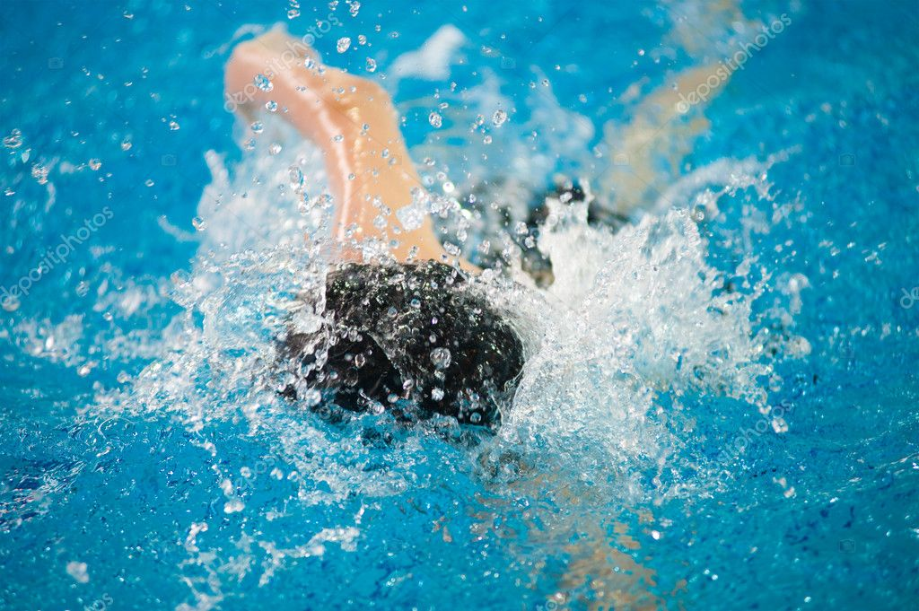A swimmer swims in an indoor pool — Stock Photo #11081074