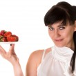 Playful woman with strawberries on plate — Stock Photo #10992606