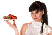 Playful woman with strawberries on plate — Stock Photo