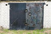 Black metal garage gate with three big locks — Stock Photo