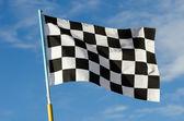 Karierte flagge mit blauem himmel — Stockfoto