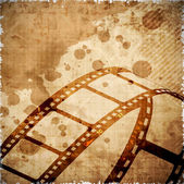Illustration of a film stripe or film reel on grungy brown movie background. EPS 10 — Stock Vector