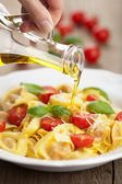 Olive oil pouring over tortellini with cheese and tomatoes — Stock Photo
