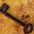 The old key on the textured paper - Stock Photo