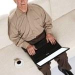 uśmiechnięty podeszłym wieku starszy mężczyzna z laptopa w domu — Zdjęcie stockowe