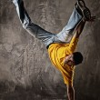 Young man dancing against grunge wall — Stock Photo