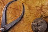 Antique tongs with a gears on the old textured paper — Stock Photo