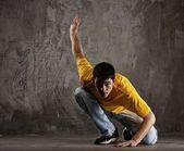 Jonge man dansen tegen grunge muur — Stockfoto