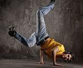 Ung man dansar mot grunge vägg — Stockfoto