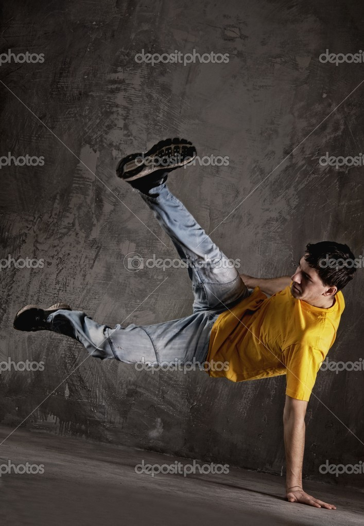 Young man dancing against grunge wall  Stock Photo #12352821