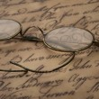 Old glasses on the vintage document — Stock Photo