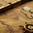 Stock Photo: Steering wheel, glasses and spyglass on the old map