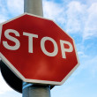 Stop sign against blue sky - Stock Photo