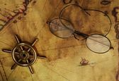 Glasses and sea wheel on the old map — Stock Photo
