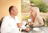 Middle-aged couple drinking coffee outdoors — Stock Photo