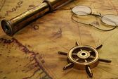 Steering wheel, glasses and spyglass on the old map — Stock Photo