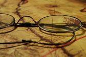 在老地图上眼镜 — 图库照片