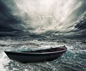 Abandoned boat in stormy sea — Stock fotografie