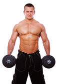 Portrait of strong man posing in gym with dumbbels — Stock Photo