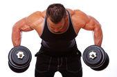 Portrait d'un homme fort qui pose en salle de gym avec haltères — Photo