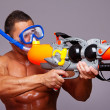 Muscular man with water gun and with swimming equipments — Stock Photo