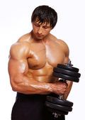 Portrait of muscle man doing exercises with dumbbells — Stock Photo