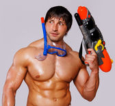 Portrait of man with water gun posing in the beach — Stock Photo