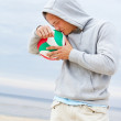 Portrait of man posing on the beach with ball — Stock Photo