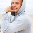 Portrait of man smiling and sitting on the beach — Stock Photo