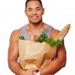Portrait of muscle man posing in studio with food — Stock Photo