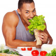 Portrait of muscle man posing in studio with food — Stockfoto
