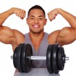 Portrait of smiling man in grey shirt with dumbbells — Stock Photo