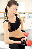 Smiling young woman workout in gym — Stock Photo