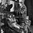 Woman in fur coat  at the mirror in  Luxurious classical interio - 图库照片