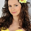Beautiful woman in a yellow dress with flower in her hair. - 