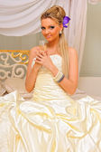 The bride with glass of champagne in the luxuriant inteior. — Stock Photo