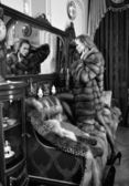 Woman in fur coat at the mirror in Luxurious classical interio — Stock Photo