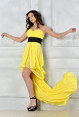 Beautiful woman in yellow evening dress. — Stock Photo