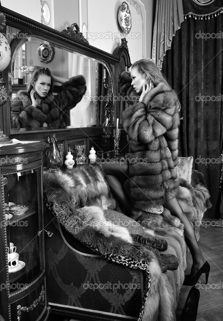 Beautiful naked woman in fur coat  at the mirror. Luxurious classical interior. — Stock Photo #11422142