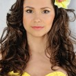 Stock Photo: Beautiful woman in a yellow dress with flower in her hair.