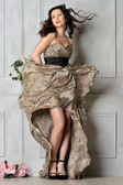 Beautiful woman in long leopard dress. — Stock Photo