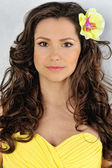 Beautiful woman in a yellow dress with flower in her hair. — Stock Photo