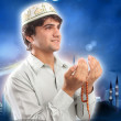Young man holding a rosary in a pose of praying and asking — Stock Photo