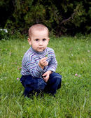 Beautiful little boy playing with a flower — Стоковое фото