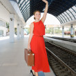 Woman with a suitcase at the railway station — Stock Photo