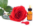 Bottles of essential oil and red rose — Stock Photo